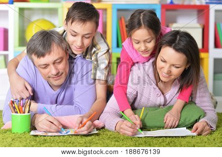 Big family lying on floor and drawing pictures together
