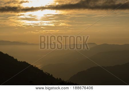Sunrise scene as seen from Okhrey Sikkim India. Sun rising from the back of mountain with orange glow. Fog in the middleground of the picture.