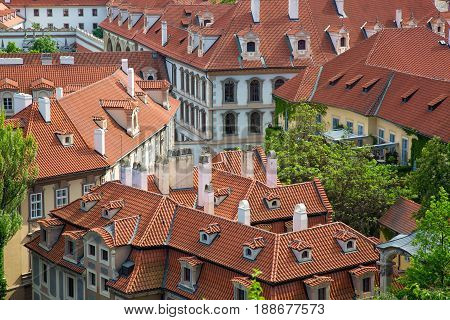 Houses with traditional red roofs and trees in Prague Mala Strana district in the Czech Republic.