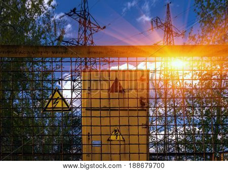 electricity. Sign dangerously high voltage on the background of high-voltage lines at sunset