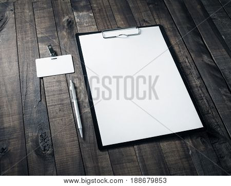 Blank letterhead badge and pen on wooden table background. Mock up for ID. Blank template for branding identity for designers.