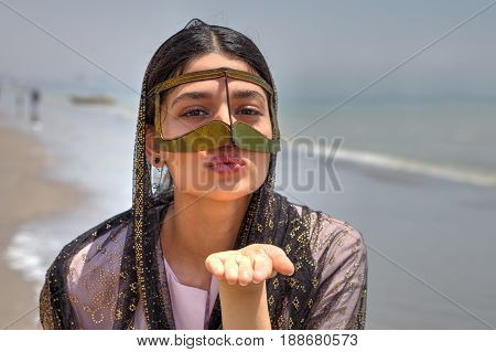 An Iranian girl in a hijab and a traditional mask of Muslims in southern Iran sends an air kiss Bander Abbas Hormozgan Iran the Persian Gulf coast.