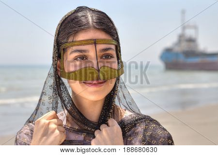 Young Iranian woman in traditional mask of Muslim women in southern Iran smiling standing on the shore of the Persian Gulf in Hormozgan province close-up portrait.
