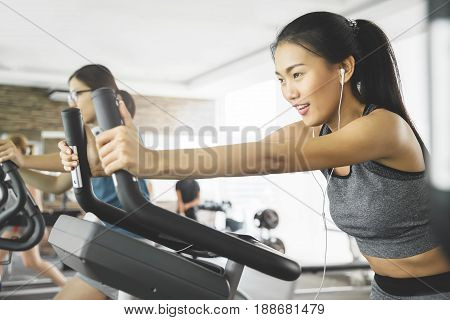 Asian woman with earphones on exercise bike at the gym.