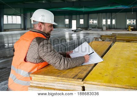 Construction supervisor checks the interior of a new warehouse being constructed with a plan in his hand, wearing a safety helmet and vest