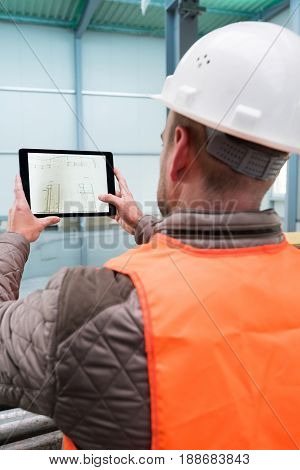 Construction supervisor checks the interior of a new warehouse being constructed with a digital tablet showing a map in his hand, wearing a safety helmet and vest. Focus on the digital tablets, the contents on its screen can easily be replaced by your con