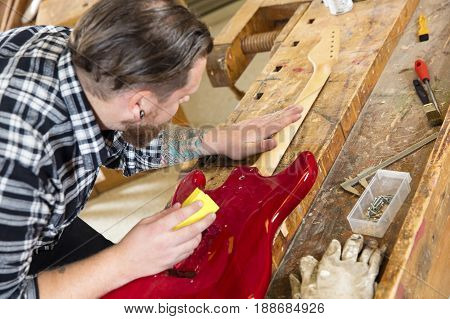 Close-up of carpenter using sanding paper on a guitar neck in a workshop for wood. Hard working man with tattoo and beard working with musical instrument restoration.