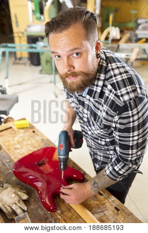 Environmental portrait of young adult craftsman who works with a guitar in a workshop for wood work and painting. Using a drill to screw.