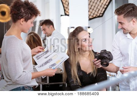 Professional model talking with fashion photographer at backstage