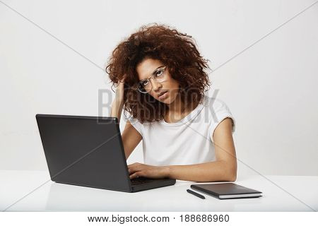 Tired african businesswoman thinking working at laptop over white background. Copy space.