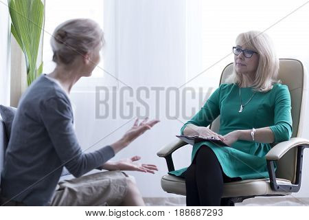 Worried woman talking about problems on session with psychologist