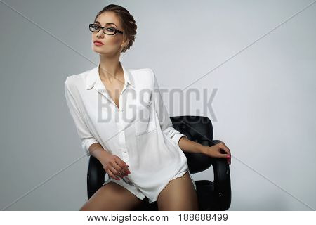 Beautiful Elegant Young Bussines Woman Sitting On The Black Leather Office Chair In The Studio With