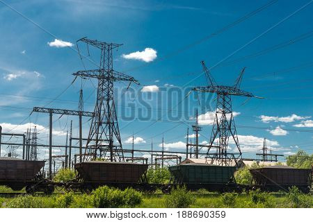 Freight train is passing by thermal power stations and power lines. Distribution electric substation.