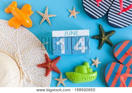 June 14th. Image of june 14 calendar on blue background with summer beach, traveler outfit and accessories. Summer day.