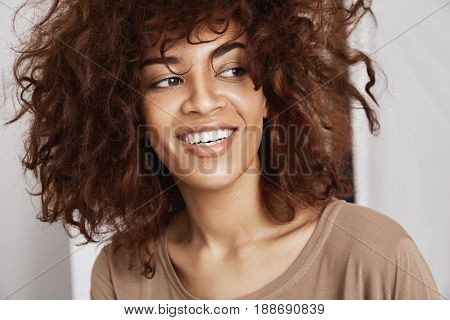 Portrait of young sincere beautiful african girl with curly hair smiling. White background.