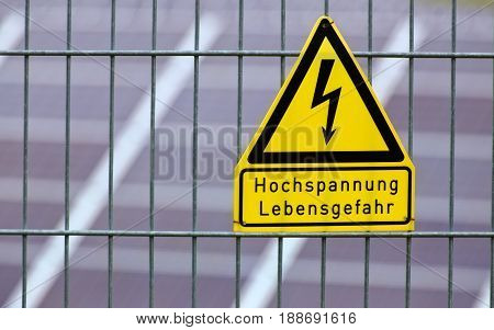 Sign With The Words High Voltage - Danger To Life In German In Front Of Solar Panels