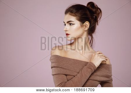 Young beautiful tender girl with makeup posing in profile over pink background.Copy space.