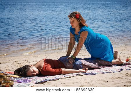 Beautiful female receiving energy sound massage with singing bowls and body massage on a river bank at spring sunny day