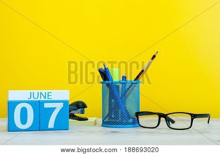 June 7th. Day 7 of month, calendar on yellow background with office suplies. Summer time at work.