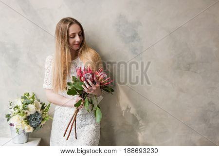 Woman with bouquet of protea king flower on wall background. Beautiful girl's gift, bouquets delivery, floristic shop concept