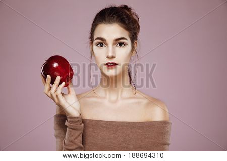 Young attactive girl looking at camera holding red apple over pink background. Copy space.