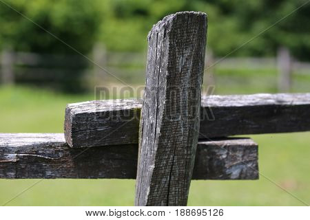Closeup of country style fence detail dividing a green grassy meadow. Shallow depth of field