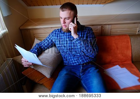 Discussing That Document. Serious Mature Man Holding Paper And Talking On The Mobile Phone While Sit