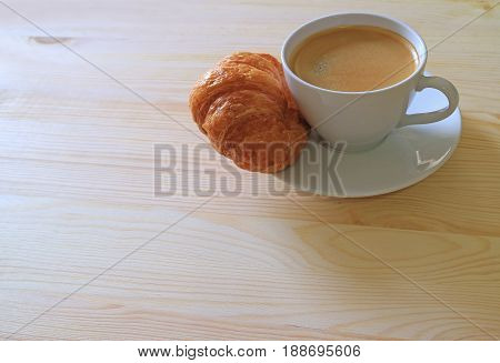 One Cup of Hot Coffee and a Butter Croissant on Wooden Table, with Free Space for Text or Design