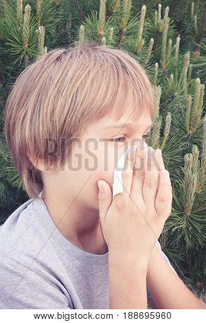 Child blowing his nose with tissue paper at the park. Healthcare, medicine, allergy concept