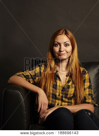 Attractive young woman with a funny grimace sitting on black sofa on black background