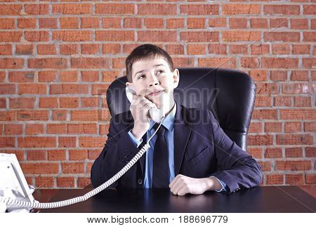 Boy sitting in a chair at the boss's table talking on the phone