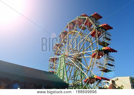 Ferris wheel in market with sunlight and clean sky background