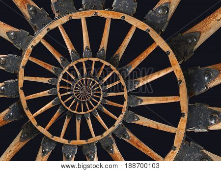 Abstract spiral wooden wagon cannon wheel black metal brackets rivets. Wheel wooden spokes fractal background. Horse vehicle wheel abstract pattern spiral background Wheel spiral Isolated on black