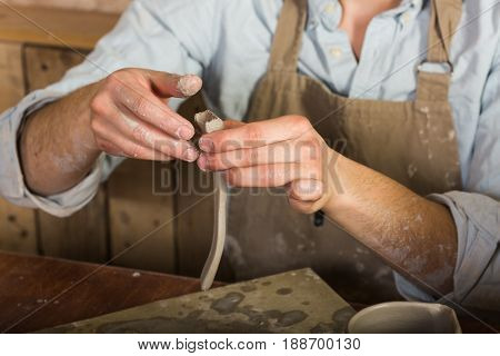 potter, stoneware, ceramics art concept - closeup on master hands working with some piece of clay, male works at a workshop near table, craftsman fingers forming the handle from raw fireclay