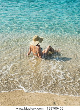 Beautiful slim senior woman tourist in bikini and hat sitting on sand enjoying clear sea waters at Meditteranean resort of Turkey in Alanya, Kleopatra beach