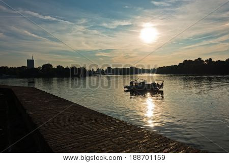 Lovely boat at sunset, confluence of Sava and Danube river in Belgrade, Serbia