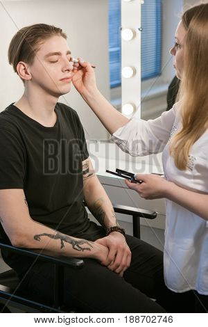 Woman putting cosmetics on man's eyes with brush. Vertical indoors shot. Male beauty , gender equality , stage makeup concept.