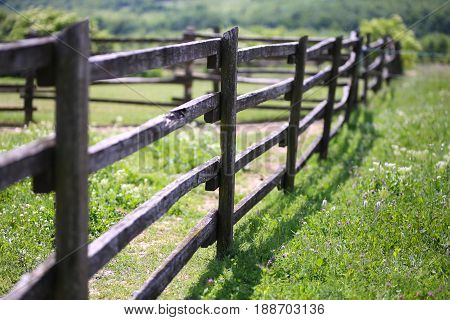 Closeup of wooden fence on a corral farmland rural scene. Shallow depth of field
