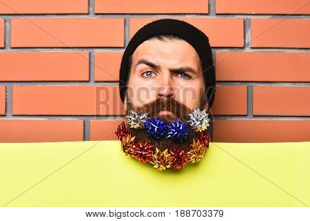 Bearded man long beard. Brutal caucasian squinting hipster with colorful gift decoration stars in moustache yellow paper sheet on brown brick wall studio background poster
