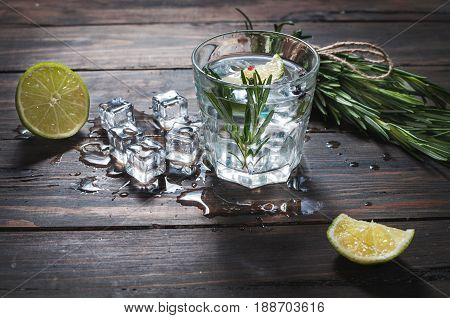 Alcoholic drink - gin tonic cocktail - with lime rosemary and ice on rustic wooden table.
