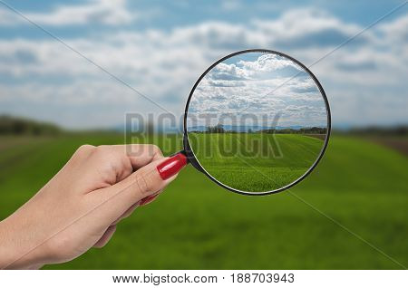out of focus nature with farmlands and a hand holding a magnifying glass that correct the vision