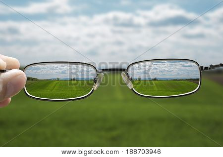 out of focus nature with farmlands and a hand holding a glasses that correct the vision