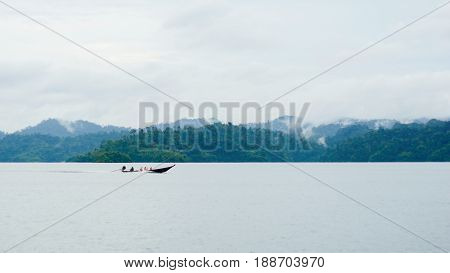 Landscape with long tail boat drive on dam and mountain background