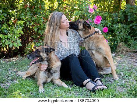 woman and belgian shepherd malinois in a garden