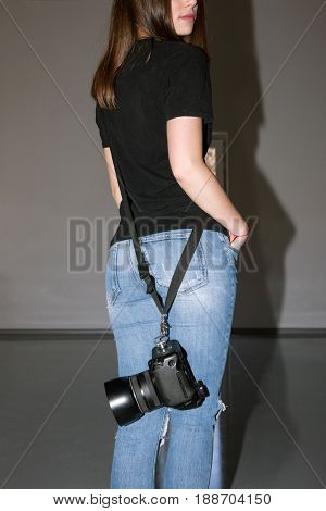 Unrecognizable photographer holding photo camera on belt. Casual woman in jeans with professional equipment back view