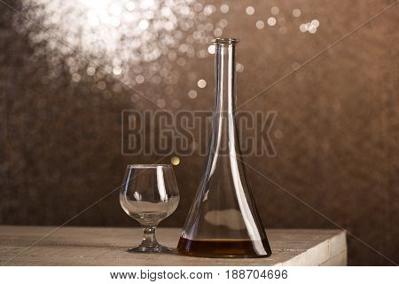 Glass Near Cone Bottle With Alcohol Beverage On Wooden Table