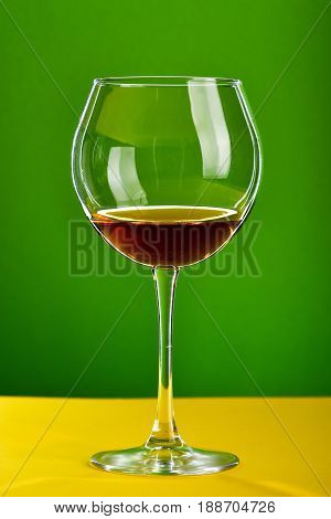 Glass Of Brown Alcoholic Beverage Standing On Yellow Surface