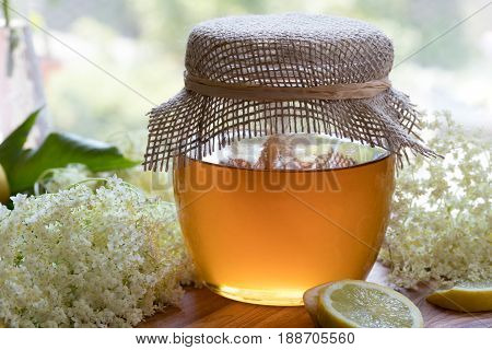 Ingredients for making a natural elder flower syrup - fresh elder flowers a jar of honey and lemon