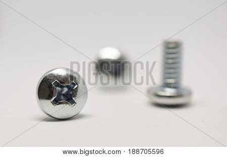 Close up shot of shiney silver screws on a white background