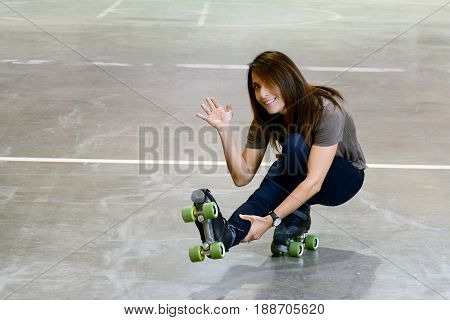 woman doing shoot the duck move on quad roller skates